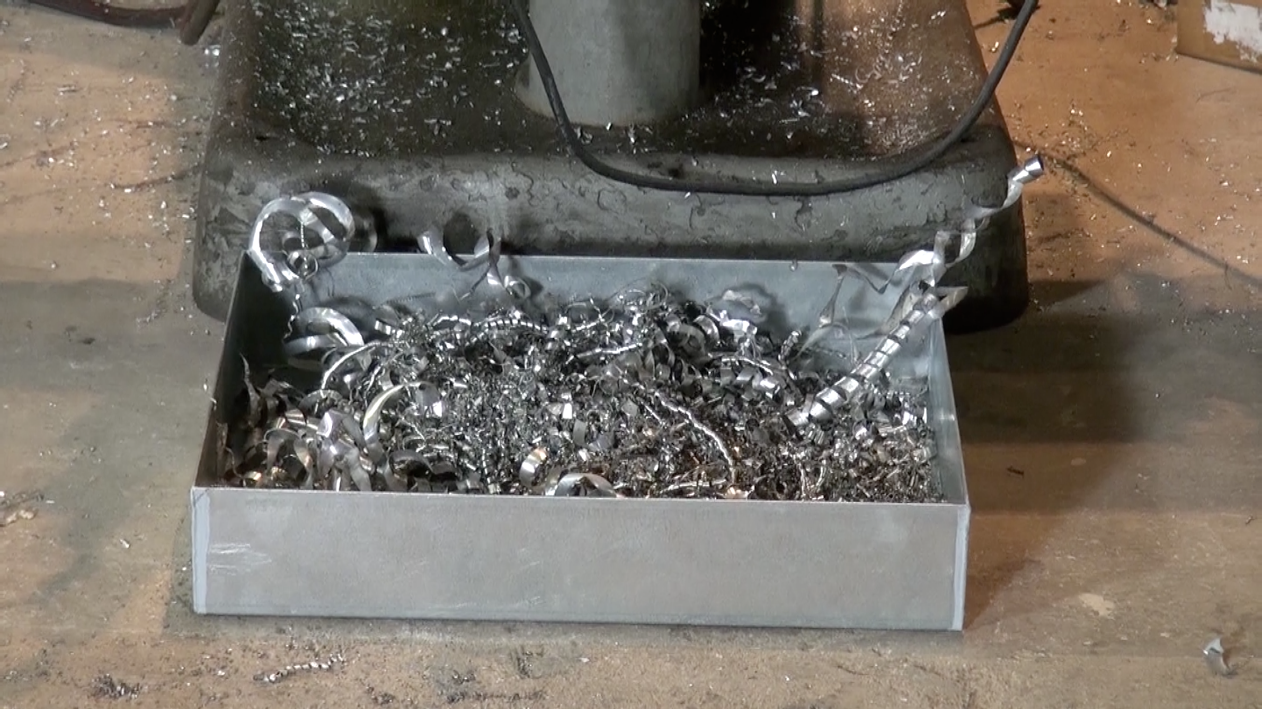 A drip tray is containing part shavings.
