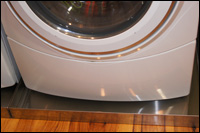 Drip pan under washer to prevent water damage and mold growth